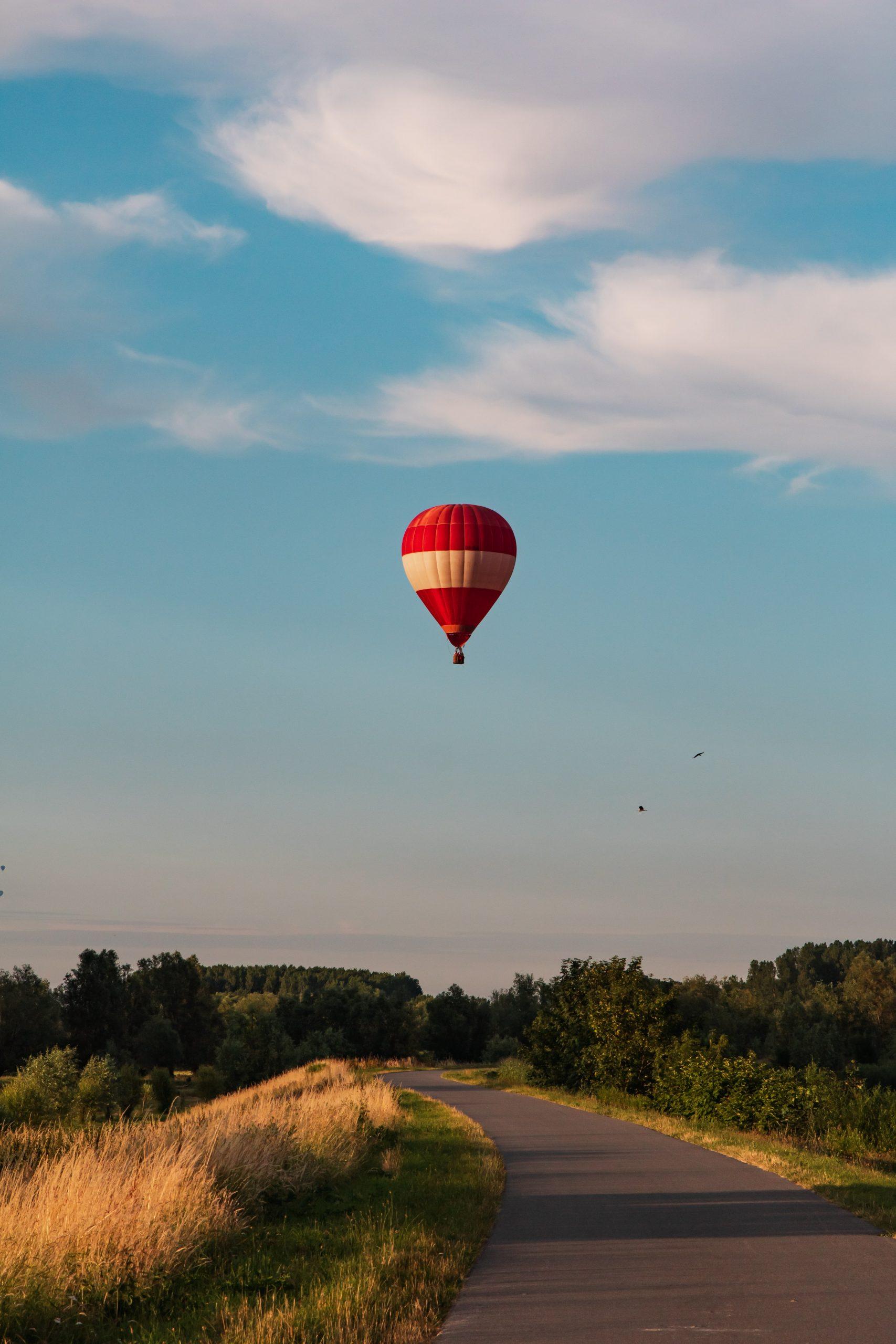 Hot air balloon soaring above a long road